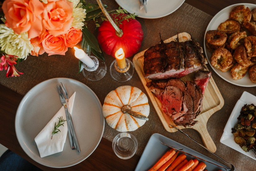 Flat Lay product photography of thanksgiving dinner set up with roast beef, pudding, carrots, pumpkin and matching cutlery in Vancouver, BC Canada