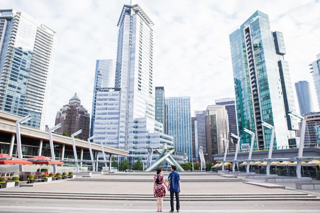 Urban engagement session of couple at Jack poole plaza while holding hands with the Vancouver financial district in the background