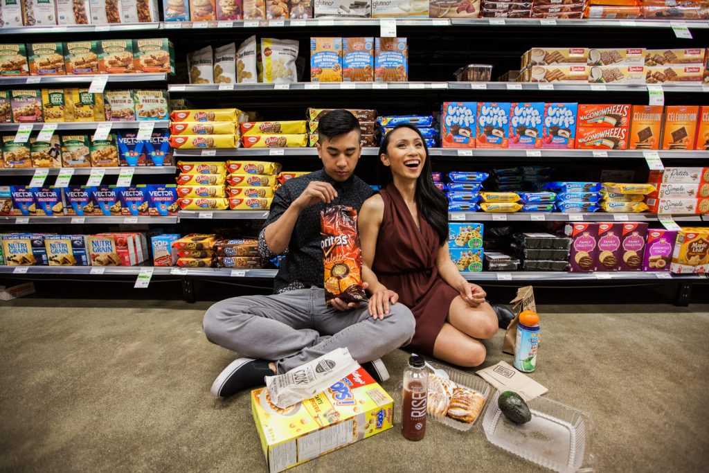 Unique engagement session in a grocery store where couple is seen eating their favourite snacks
