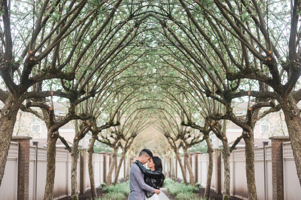 Unique engagement session of couple holding each other against a line of trees