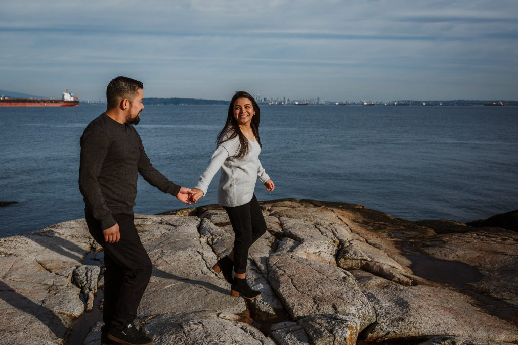 Lighthouse engagement session of couple casually walking on the rocks