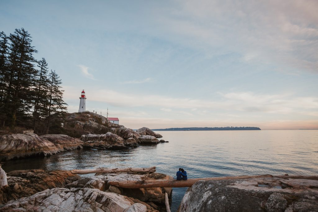 Lighthouse park engagement session during sunset overlooking the Vancouver horizon and lighthouse
