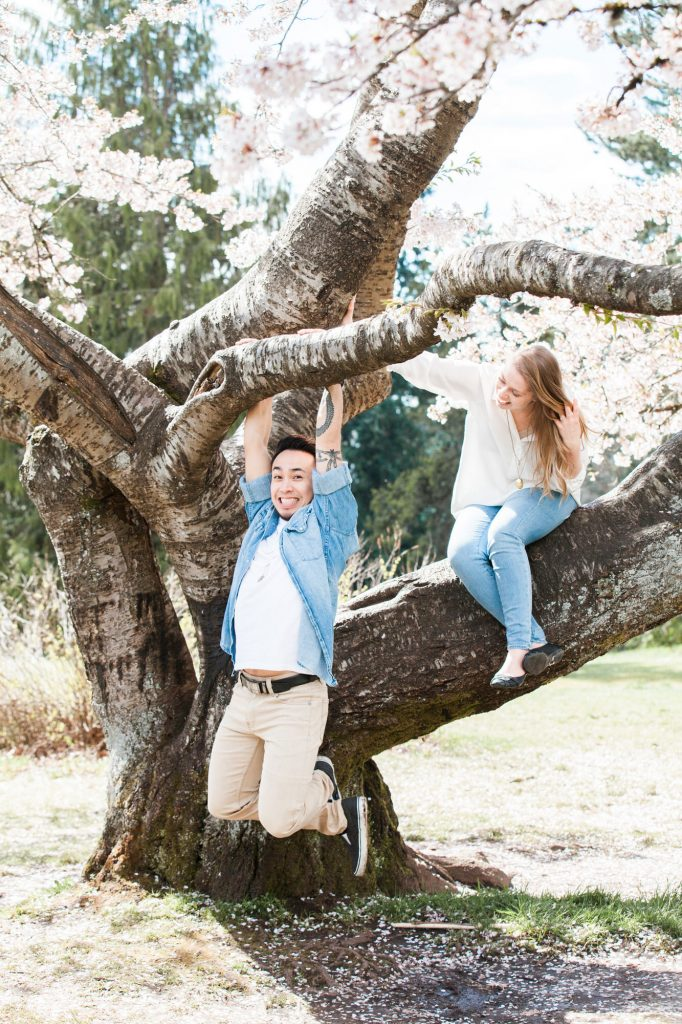 Couple hanging on a cherry blossom tree during their spring engagement session