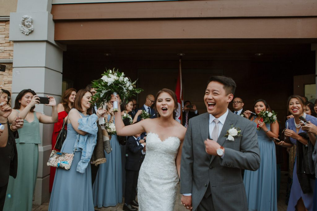 Bride and groom exiting the church after getting married in coquitlam