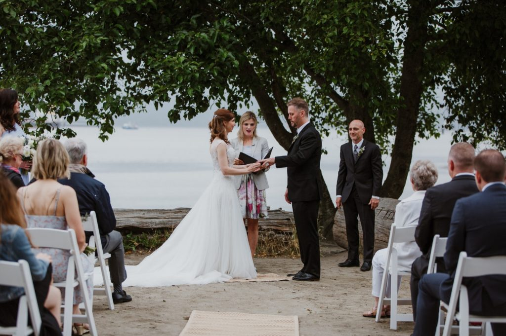 candid photo of bride putting on the ring on the groom in spanish banks