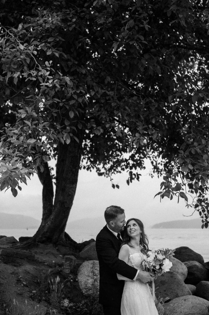 Black and white candid photo of the bride and groom hugging and smiling at each other in spanish banks