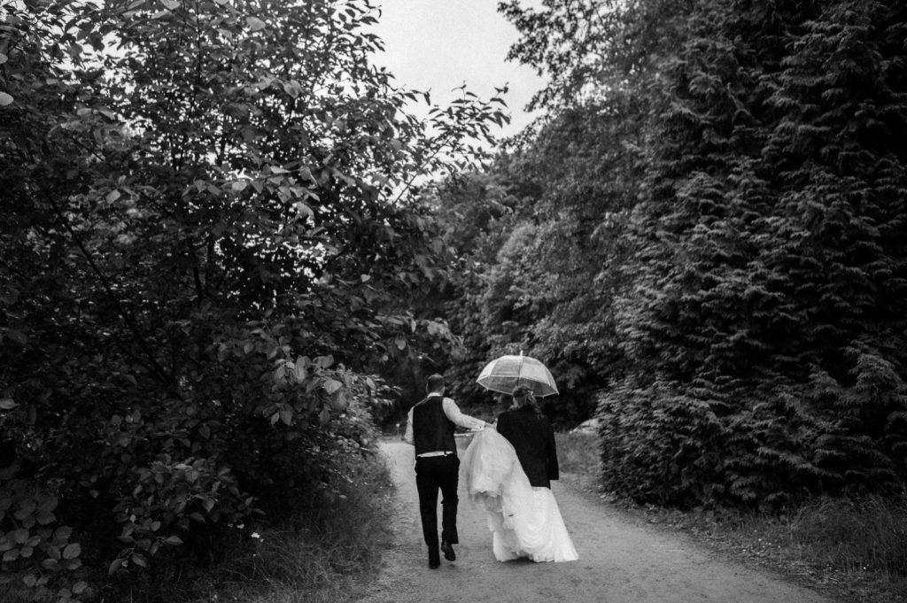Black and white photo of the bride and groom walking to the reception in spanish banks