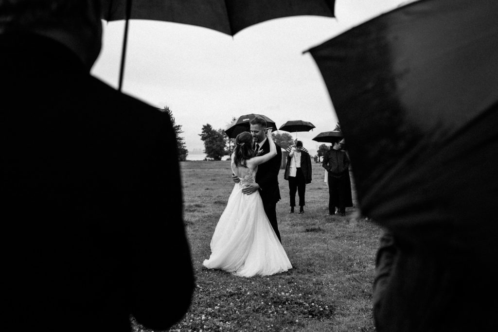Black and white candid romantic photo of bride and grooms first dance under the rain in spanish banks