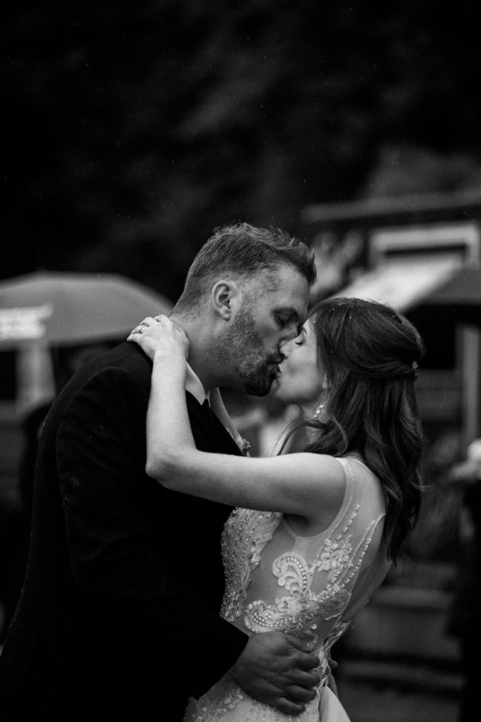 Black and white photo of the bride and groom kissing under the rain during their first dance in spanish banks