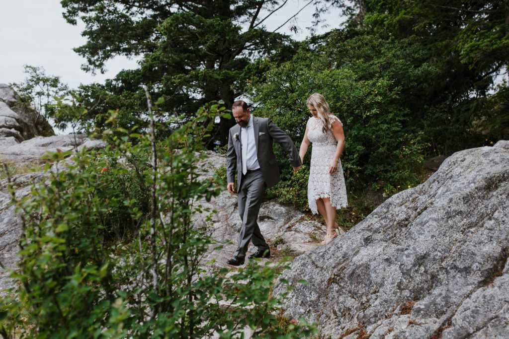 Candid photograph of bride and groom walking in whytecliff park