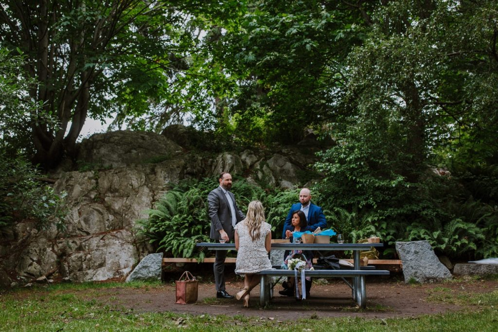 Wide angle photo of the bride and groom candidly hanging out with their witnesses during their surprise picnic